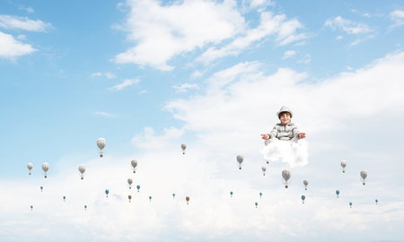 Young little boy keeping eyes closed and looking concentrated while meditating among flying balloons in the air with cloudy skyscape on background. Imagens