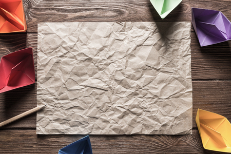 Crumpled brown paper sheet and pencil on wooden table Stock Photo - 121359703