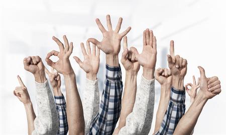 Fila de manos de hombre mostrando varios gestos. Ok, señalar con el dedo, victoria, dedos abiertos, puño cerrado y signos de pulgar hacia arriba. Manos humanas gesticulando sobre fondo claro borroso. Muchos brazos alzados juntos.