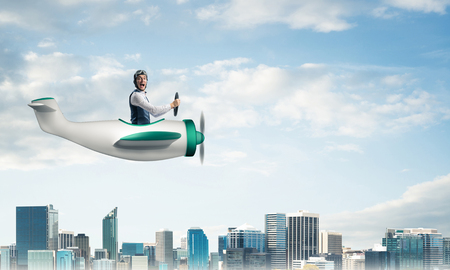 Scared pilot with open mouth sitting in cabin of small airplane. Funny man in aviator hat and goggles driving propeller plane above city. Modern metropolis with high buildings and towers.