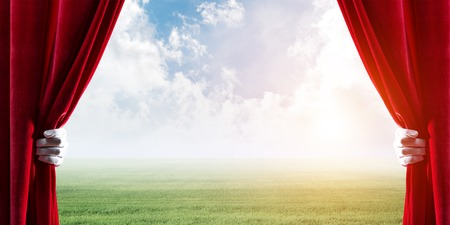 Human hand opens red velvet curtain to landscape with green grass