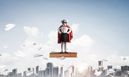 Young girl in superhero costume standing on old floating book. Mixed media