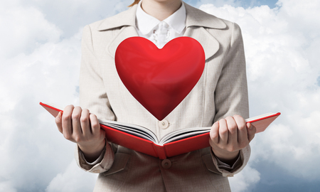 Beautiful woman showing red heart above opened notebook. Love and tenderness, valentines holiday and fall in love concept. Close up woman hands holding open book on background of skyscape. 스톡 콘텐츠