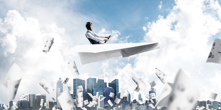 Business accounting and statistics concept with funny pilot. Aviator driving paper plane above falling paper sheets with infographics. Young man flying in paper airplane above paperwork. Stok Fotoğraf