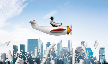 Businessman in aviator hat and goggles driving propeller plane above downtown. Papers falling down on background of skyscrapers. Funny man having fun in small airplane. Blue sky with clouds. Stock Photo