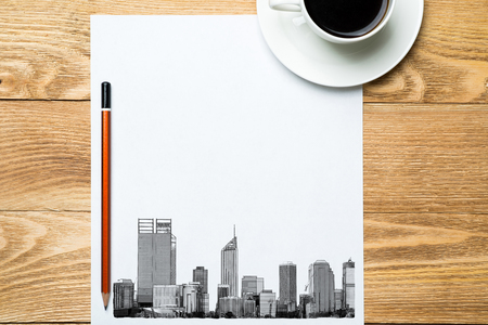 Wooden table with coffee cup and architectural sketches on notepad