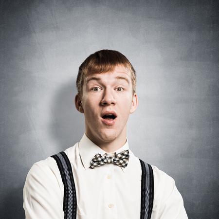 Verblüffter Teenager mit offenem Mund. Emotionaler rothaariger Junge hat Gesichtsausdruck schockiert. Porträt des Mannes trägt weißes Hemd, Fliege und Hosenträger auf dem Hintergrund der grauen Wand. Standard-Bild