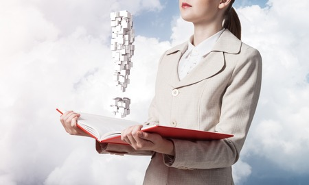 Attractive woman holding open notebook with exclamation mark. Business consultation and legal assistance. Elegant young woman in white business suit with open book in hands on background of blue sky. Banco de Imagens