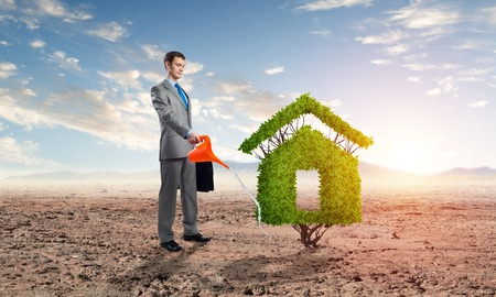 Businessman watering green plant in shape of house in desert. Business growth and development. Nature landscape with dry soil and blue sky. Green and eco friendly technology. Real estate agency Banco de Imagens - 121719857