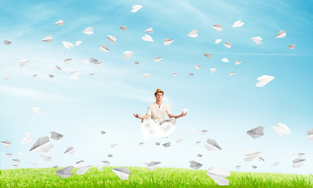 Young man keeping eyes closed and looking concentrated while meditating on cloud among flying paper planes with bright and beautiful landscape on background.