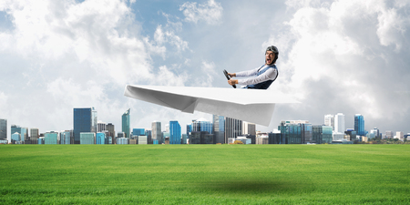 Young pilot sitting in big paper plane. Modern urban architecture with high skyscrapers on background. Man in paper airplane flying low above green field. Megalopolis panorama with green grass Stock Photo