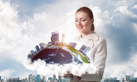 Smiling woman looking at earth globe above open book. Global business concept. Elegant young woman in white business suit holding open book on background of cityscape and cloudy blue sky. Stock Photo