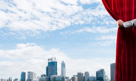 Hand of businessman opening red velvet curtain and cityscape at background Stock Photo - 121891323