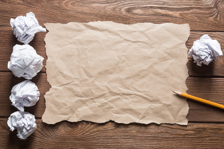 Crumpled brown paper sheet and pencil on wooden table Stock Photo - 121891502