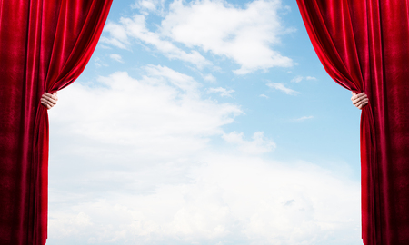 Human hand opens red velvet curtain on blue sky background Stock Photo - 121926980