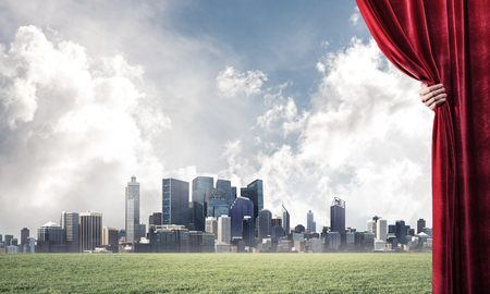Human hand opens red velvet curtain to cityscape and green meadow