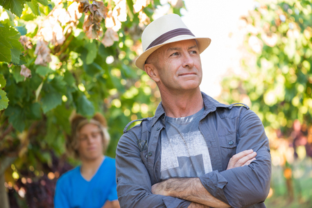 Successful winemaker at their vineyard. Handsome senior man in straw hat and shirt posing in garden. Traditional family winemaker business. Confident vintner with arms folded standing at vine row. Banco de Imagens