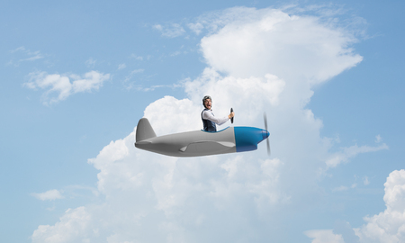 Happy pilot driving small propeller plane on background of blue sky with clouds. Traveling around the world by airplane. Funny man flying in small airplane. Cloudscape background with fluffy clouds.
