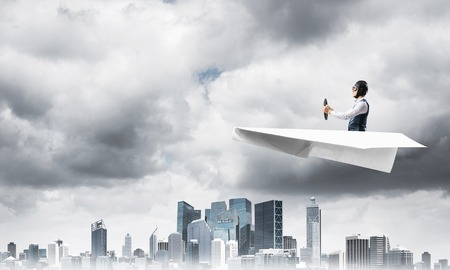 Businessman in aviator hat and goggles driving paper plane in storm. Crisis management concept. Side view of pilot in small paper airplane. Megalopolis panorama with dramatic dark cloudy skyscape. 版權商用圖片 - 122089596