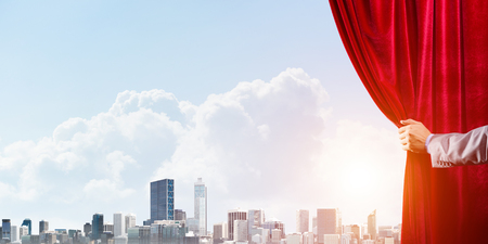 Human hand opens red velvet curtain to modern cityscape and cloudy sky Stock Photo - 122089455