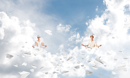 Young couple keeping eyes closed and looking concentrated while meditating among flying paper planes in the air with cloudy skyscape on background.