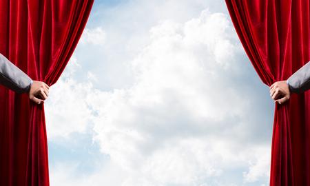Menselijke hand opent rood fluwelen gordijn op blauwe hemelachtergrond