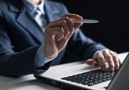 Man in business suit sitting at desk and working at laptop. Close-up of human hand with pen pointing at empty space. Corporative business and professional occupation. Modern digital technology Banco de Imagens