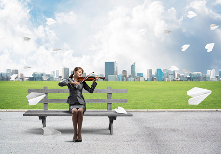 Young woman with violin sitting on wooden bench. Attractive businesslady playing violin. Modern cityline panorama with flying paper planes. Musician practicing and performing outdoors.
