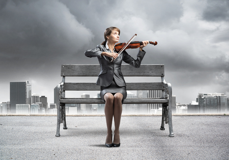 Young woman with violin sitting on wooden bench. Attractive businesslady playing violin on background modern cityline panorama with cloudy storm sky. Musician practicing and performing outdoors. Stock Photo