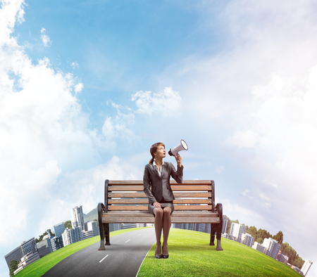 Business woman with megaphone sitting on wooden bench. Female speaker shouting in loudspeaker outdoors. Cityscape panorama with round horizon of world. Business marketing and announcement.