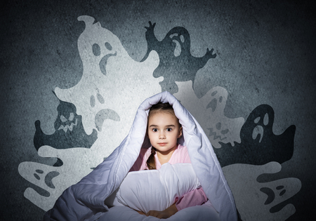 Scared girl with pillow hiding under blanket. Startled kid sitting in his bed at home. Little girl afraid of dark. Covered child not sleep at night. Fearful girl in pajamas and imaginary monsters.