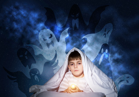 Scared boy with flashlight hiding under blanket. Frightened kid lying in his bed at home. Night terrors of child. Boy in pajamas and boo ghosts silhouettes back on wall. Kids nightmare fantasy