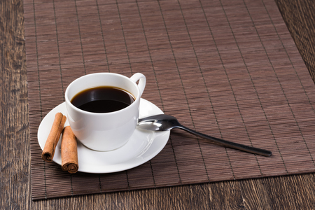 Cup of black coffee on wooden table with bamboo mat. Cinnamon sticks on white porcelain saucer with spoon. Close up natural aromatic hot drink in restaurant. Morning coffee break. Stock Photo