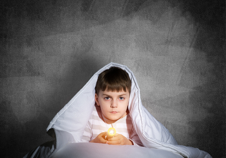 Serious child with flashlight hiding under blanket. Attentive kid lying in his bed at home. Fear to sleep in darkness at night. Portrait of little boy in pajamas on background of grey wall. Stock Photo