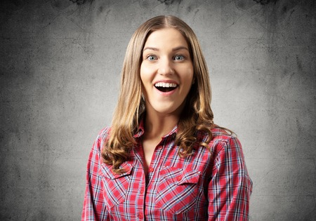 Happy charming girl smiling wide. Emotional young woman has surprised facial expression. Portrait of delighting girl wears red checkered shirt on grey background. People emotion and expression. Stok Fotoğraf