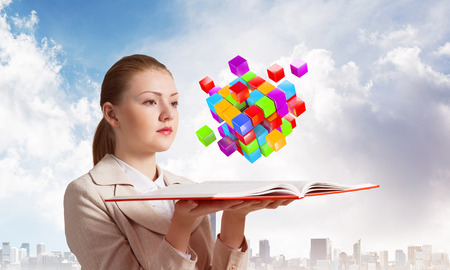Woman looks at flying colorful 3d cubes above open book. Hi-tech concept with virtual reality abstract square element. Businesswoman with open book. Elegant lady on background of business downtown