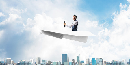 Business leadership and motivation concept with pilot sitting in paper airplane. Funny man in aviator hat and goggles driving paper plane above city. Modern megapolis with high buildings.