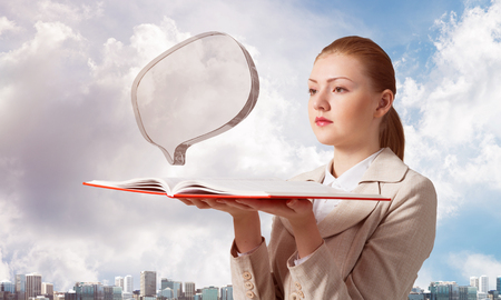 Woman looks at transparent speech bubble above opened notebook. Business communication and conversation. Elegant girl with book on background of cityscape and cloudy blue sky.