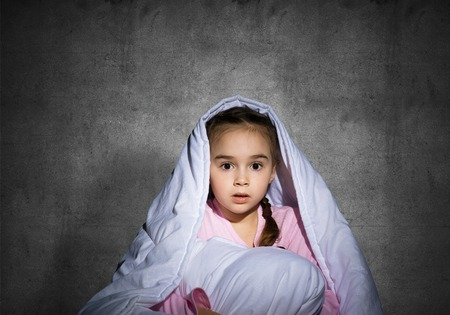 Frightened girl hiding under blanket. Scared kid lying in his bed at home. Fear of the dark. Beautiful little girl can not sleep at night. Portrait of child in pajamas on background of grey wall. 免版税图像