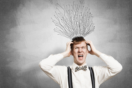 Stressful redhead student keeps hands on head. Young man in panic on background of grey wall with many arrows as hair sketch overhead. Conflict priorities and crisis. Nervous teenager screaming.