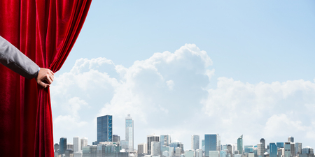 Human hand opens red velvet curtain to modern cityscape and cloudy sky Stock Photo - 122552238