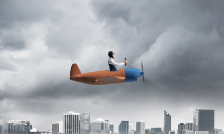 Businessman in aviator hat and goggles driving propeller plane in storm. Side view of pilot in small airplane. Megalopolis panorama with dramatic dark cloudy skyscape. Mixed media business concept.