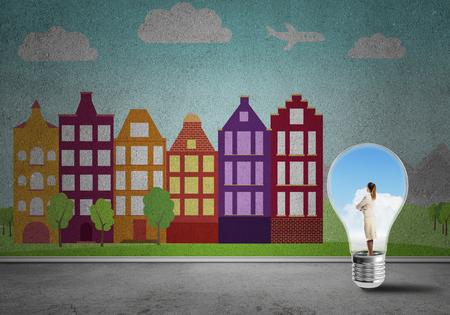 Businesswoman inside light bulb against city drawn concept Standard-Bild