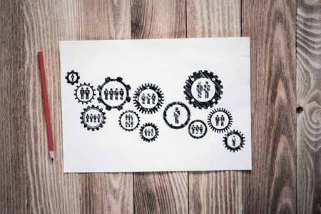 Corporate HR management pencil hand drawn with group of rotating gears and cogs. Business team building sketch on wooden surface. Top view of workplace with paper and pencil lying on wooden desk.