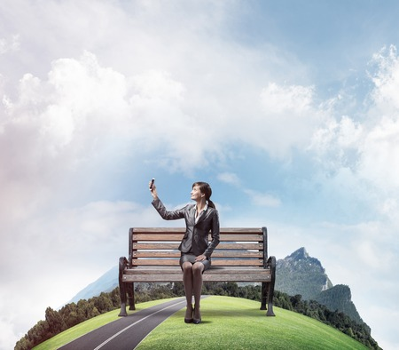 Business woman taking selfie photo or chatting with smartphone. Attractive girl showing mobile phone on wooden bench. Mobile marketing and communication. Mountains panorama with round horizon of world