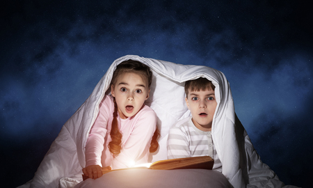 Children reading scary stories in bed before going to sleep. Little girl and boy in pajamas hiding under blanket together. Covered kids with open book not sleep at night. Fear of the dark concept