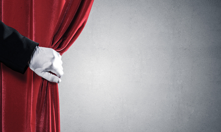Close up of hand in white glove open red velvet curtain Stockfoto