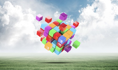 Abstract colorful cubes on green meadow. Digital technology and innovation solutions. New approach to business management. Nature landscape with green grass and blue sky. Mixed media with 3D object
