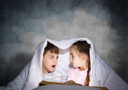 Frightened girl and boy looking at each other under blanket. Children reading magic stories in bed before going to sleep. Young sister and brother in pajamas together on background of grey wall. Stockfoto