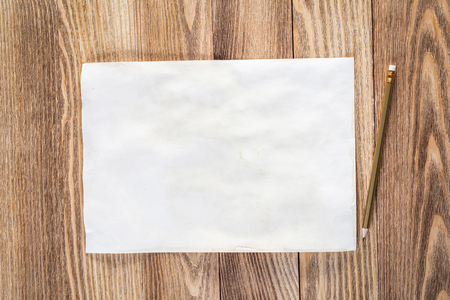 Sheet of paper lying on wooden table. Top view of rectangular blank white old paper. Textured natural wooden background. Vintage copy space for design. Artist workplace and hand drawn skills